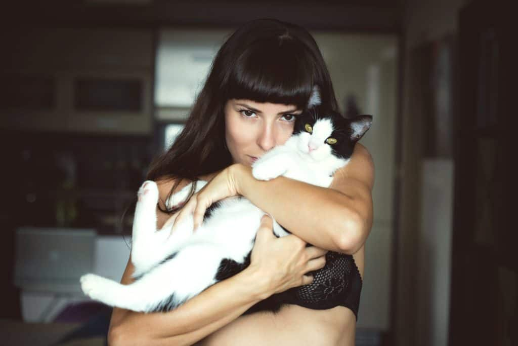woman hugging cat